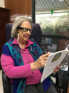 Sybil reading with her OrCam MyEye device